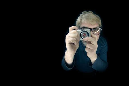 Nerdy young man taking photographs with a vintage camera - isolated on black