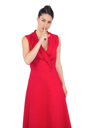 Glamorous model in red dress on white background keeping secret