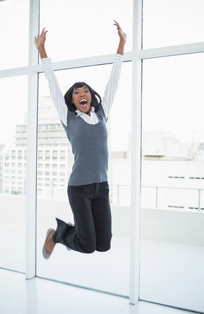 Happy businesswoman jumping in bright office