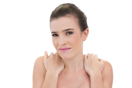 Worried natural brown haired model holding her shoulders on white