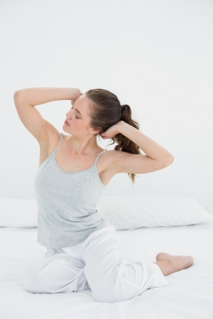 Sleepy young woman waking up in bed and stretching her arms