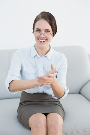 Portrait of a smiling smart woman clapping hands on sofa