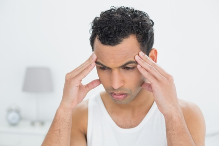 Close-up of a young man suffering from headache in bed at home