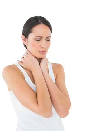 Close-up of a casual young woman suffering from neck ache over white background