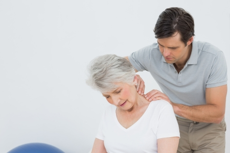 Male physiotherapist massaging a senior woman's neck in the medical office