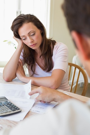 Upset young woman and man sitting with home bills at the table