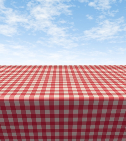 Checkered tablecloth table with a blank empty picnic cloth in perspective on a blue sunny summer sky as a symbol of food and leisure fun