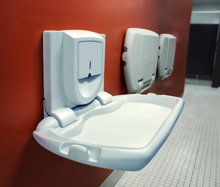 Urban parenting with a public diaper changing table mounted on a wall