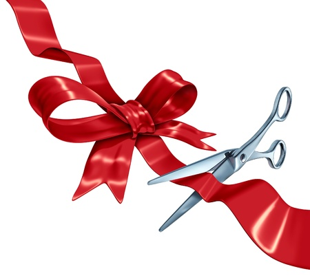 Bow and ribbon cutting with a red silk gift wrapping decoration with scissors opening the present packaging as a holiday symbol for Christmas a birthday or valentine