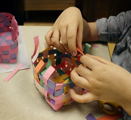 Arts and crafts with the hands of a child crafting a basket made of construction paper as a symbol of art education at schools or other creative activities for kids