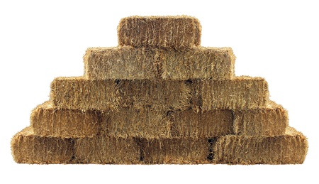 Bale of hay group in a pyramid wall pattern isolated on a white background as a country living design element and agriculture farm and farming symbol of harvest time with dried grass straw as bundled tied haystacks