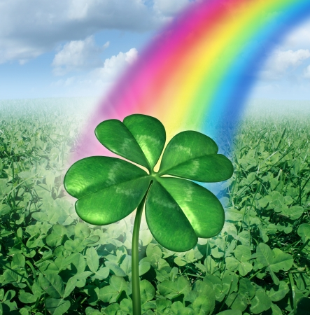 Luck concept with a four leaf clover over a field of green clovers with a rainbow from the sky shinning down as a symbol of good fortune and prosperity as a metaphore for success and opportunity