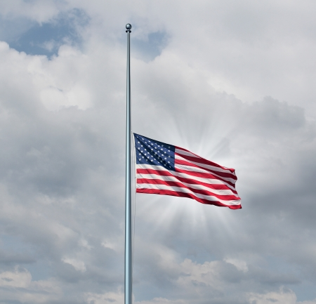 Half mast American flag concept with the symbol of the United States flying at low level on the flagpole or staff on a cloudy day with a sun glow as an icon of honor respect and mourning for fallen heros