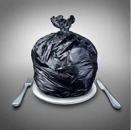 Food garbage and poor nutrition concept as a table setting with a black plastic garbage bag on a dinner plate with a knife and fork as a metaphor for a bad diet or doggy bag symbol