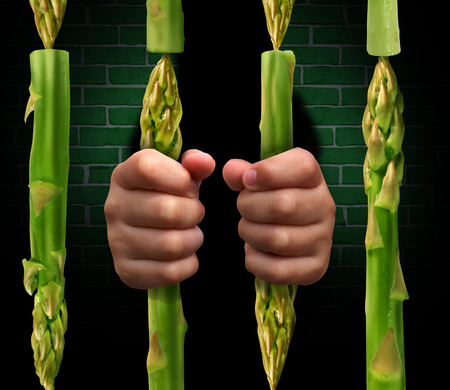 Restricted diet and calorie restriction food concept with prison bars made of asparagus vegetables and hands of a prisoner holding the jail as a dieting metaphor for the stress involved in healthy eating