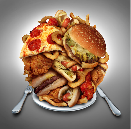 Fast food diet concept served on a plate as a mountain of greasy fried restaurant take out as onion rings burger and hot dogs with fried chicken french fries and pizza as a symbol of compulsive overeating and dieting temptation resulting in unhealthy nutr