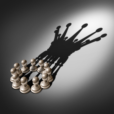 Leadership team and business group concept as an organized company of chess pawn pieces joining forces and working together united and as one in agreement to cast a shadow shaped as the crown of a king