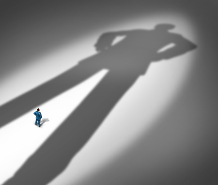 Under a shadow business metaphor for living under a powerful leader or the little guy or small business competing against giants as a businessman facing a huge darkness shaped as a giant man as a symbol of a bodyguard or guardian angel.
