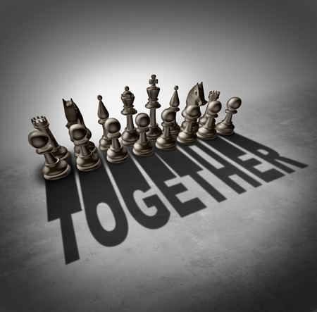 Together concept and team effort symbol as a group of chess pieces in a set casting a shadow with the word representing partnership solidarity in a company or union of workers.