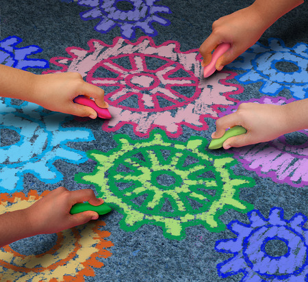 Education concept as a diverse community of children working together in friendship drawing connected gears and cog wheels with chalk as a symbol for the success of learning with a school program.