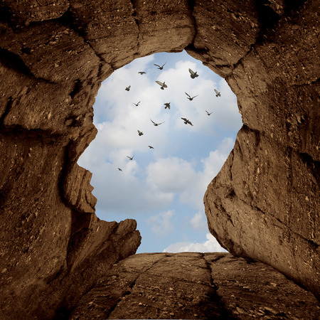 Imagination and discovery concept as a rocky cliff with an opening on top shaped as a human head as a new life metaphor and success motivation symbol with a group of birds flying high in the sky.