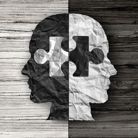 Racial ethnic social issue and equality concept or cultural justice symbol as a black and white crumpled paper shaped as a human head on old rustic wood background with a puzzle piece as a metaphor for social race issues.