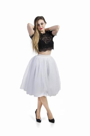 Emotional girl in white skirt posing on a white background.