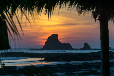 Colorful sunset on the beach in Nicaragua with a rock in the front.