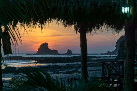 Colorful sunset on the beach in Nicaragua with a rock and banana leafes in the front.