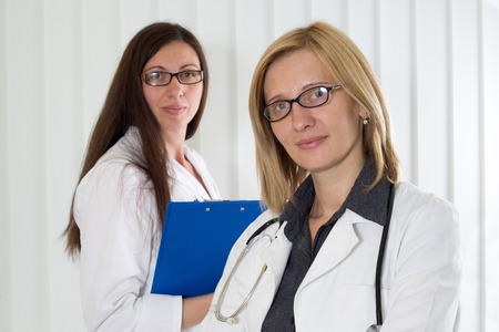 Portrait of Blonde Hair Female Doctor With Glasses and Her Medical Colleague With Clipboard in Background Smiling and Looking at Camera HalfLength Shot