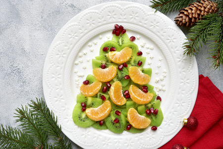 Foto de Edible christmas tree from kiwi and tangerine slices on a white plate over light slate, stone or concrete background.Top view with copy space. - Imagen libre de derechos