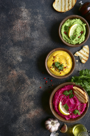 Photo pour Assortment of hummus on a dark slate, stone or concrete background.Top view with copy space. - image libre de droit