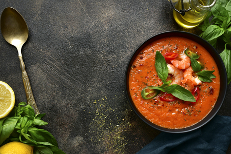 Photo for Delicious tomato soup with shrimps in a black bowl over dark slate, stone or concrete background. Top view with copy space. - Royalty Free Image