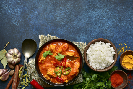 Photo pour Chicken tikka masala - traditional dish of indian cuisine in a clay bowl over dark blue slate, stone or concrete background.Top view with copy space. - image libre de droit