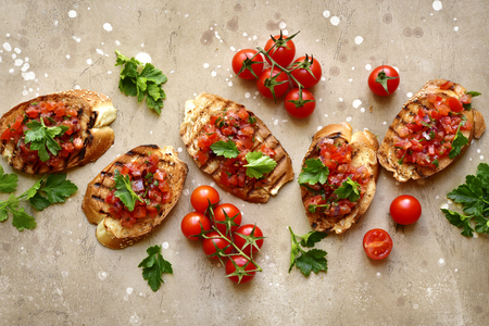 Photo pour Toasts with cherry tomatoes, red onion and olive oil on a beige or sand slate, stone or concrete background.Top view with copy space. - image libre de droit