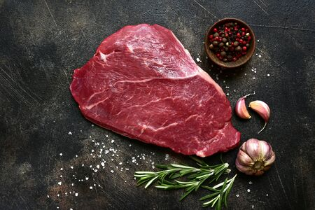 Photo pour Raw beef steak with spices on a dark slate, stone or concrete background. Top view with copy space. - image libre de droit
