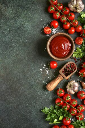 Photo for Homemade tomato sauce or ketchup on a dark green slate, stone or concrete background. Top view with copy space. - Royalty Free Image