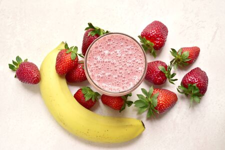 Photo pour Delicious strawberry banana smoothie in a glass with ingredients for making on a light pink slate, stone or concrete background. Top view with copy space. - image libre de droit