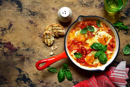 Photo for Shakshouka - traditional dish of israeli cuisine from tomatoes and eggs in a skillet on a rustic wooden background. Top view with copy space. - Royalty Free Image
