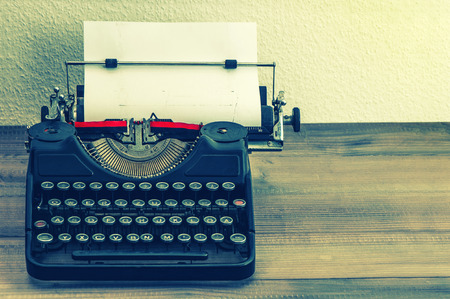 retro typewriter with white paper page on wooden table  vintage style toned picture
