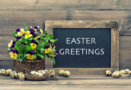 easter decoration with eggs, pansy flowers and vintage blackboard with sample text Easter Greetings  Retro style toned picture