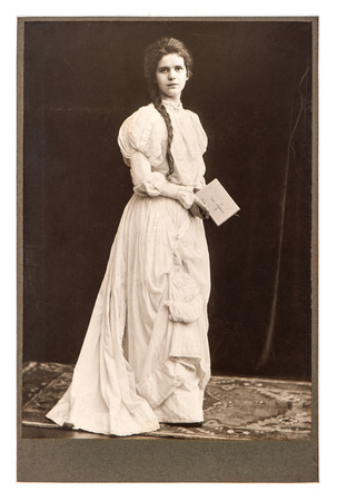 young woman in vintage dress posing with bible book  antique picture from ca  1900