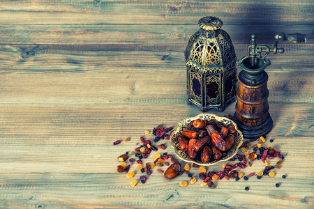 Raisins and dates on wooden background. Still life with vintage oriental lantern. Retro style toned picture