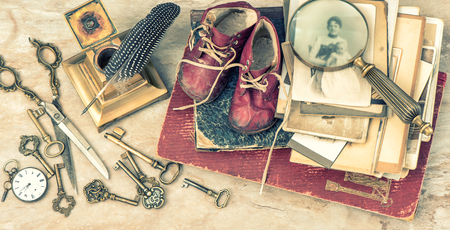 Foto de Antique books and photos, keys and writing accessories. Nostalgic still life with baby shoes. Vintage style toned picture - Imagen libre de derechos
