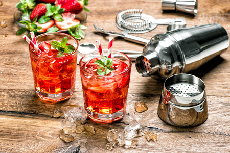 Photo pour Red drink with ice. Cocktail making bar tools, strawberry and mint leaves - image libre de droit