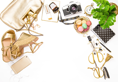 Fashion flat lay for bloggers social media. Feminine golden accessories, bag, shoes, office supplies, vintage no nae photo camera and green plant on white background