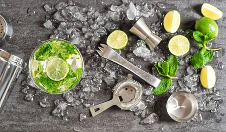 Photo pour Bar accessories and ingredients for cocktail drink lime, mint, ice. Alcoholic and nonalcoholic cold drinks - image libre de droit