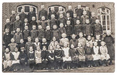 Photo pour Old photo of school classmates. Group of children and teacher outdoors. Vintage picture with original film grain and blur - image libre de droit