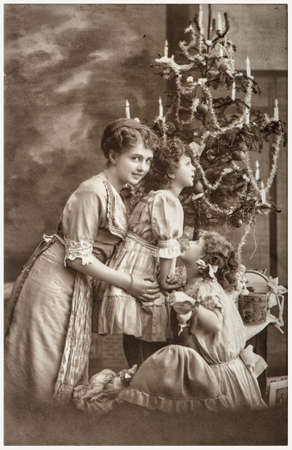 Photo for Happy family mother children with Christmas tree, gifts and vintage ornaments. Retro sepia picture with original film grain and blur - Royalty Free Image
