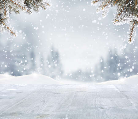 Foto de Merry christmas and happy new year greeting background with woden table .Winter landscape with fir tree - Imagen libre de derechos